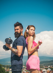 Active lifestyle concept. Beautiful slim sexy woman with good body forms wearing hot pink sportswear and doing sport fitness exercises with her handsome bearded coach.