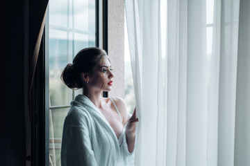 Woman looking out of the window. Morning woman.