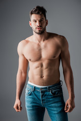 handsome sexy muscular man in jeans isolated on grey