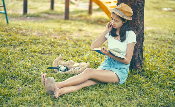 Woman sitting on a lawn under a green tree. Write and search for ideas.