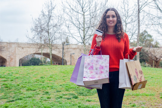 Portrait of attractive caucasian young woman with a credit card in hand with shopping bags, in the park, long curly hair. Place for your text in copy space.