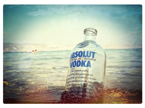 Empty bottle of famous Swedish Absolut Vodka filled with pebbles rocks