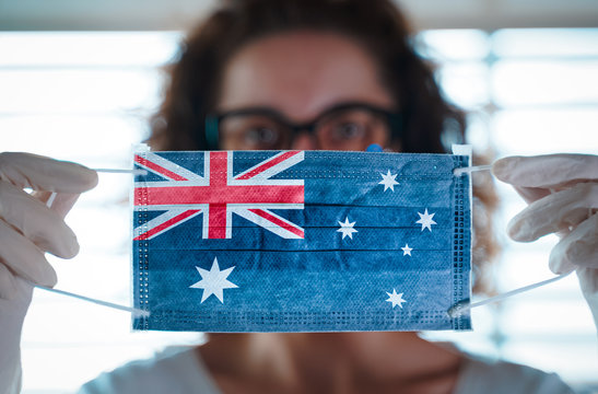 Pandemic Coronavirus. Close up of young woman with surgical mask with the flag of australia on it. Concept of Coronavirus, COVID-19, health emergency and quarantine