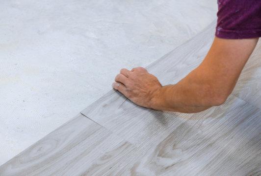 Work on laying worker installing new vinyl tile laminate floor.