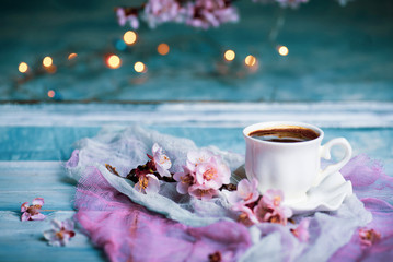 Cup of coffee and spring cherry blossom flowers