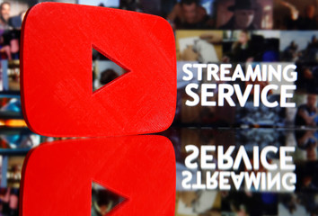 "A 3D-printed Youtube logo is seen in front of displayed ""Streaming service"" words in this illustration"