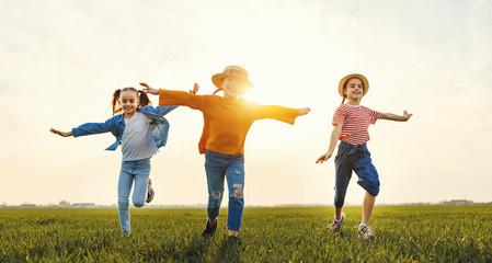 Happy children running in field.