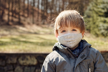 Small boy in a garden outside during a pandemic wearing fabric facemask, looking directly in front Wall mural