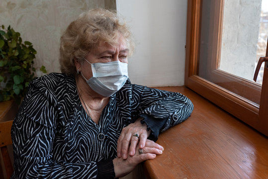 An elderly woman in a protective mask sits at home and looks out the window. Quarantine, self-isolation, the health hazard of the elderly during the coronavirus pandemic.