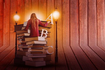 Pile of Books with Student and Lit Lamps on Wooden Background
