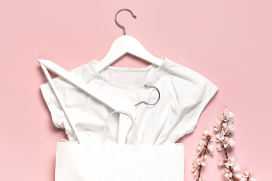 Creative spring sale concept. White wooden hangers with spring flowers white shirt paper bag on pink background top view flat lay. Fashion spring discounts shopping sale store promo design