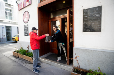Waitress Julia serves a customer with food at the entrance of Restaurant-Bar Steindl in Vienna