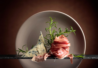 Fototapete - Prosciutto or spanish jamon with blue cheese and rosemary.