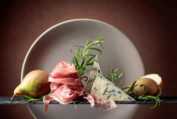 Fototapete - Prosciutto or spanish jamon with blue cheese, pears and rosemary.