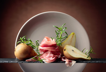 Fototapete - Prosciutto or spanish jamon with pears and sprigs of rosemary.