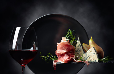 Wall Mural - Glass of red wine with traditional mediterranean snacks.