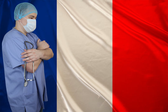 male doctor in a medical mask with a stethoscope in his hand against the background of the silk national flag of France, concept of national medical care, health, insurance, tourism