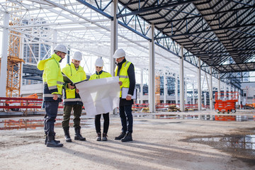 Group of engineers with blueprints standing on construction site.