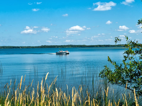 Beautiful Minnesota lake scene from the shore includes a passing poWooden bird watching shelter hut for observing wildlife in Port Aransas, Texas on a sunny day, includes a handicap accessible ramp.