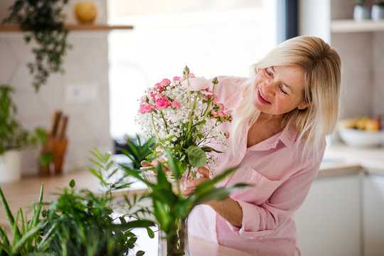 Portrait of senior woman arranging flowers in vase indoors at home.