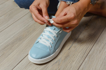 Women's hands tie the laces on the sneakers. Comfortable shoes. Sport