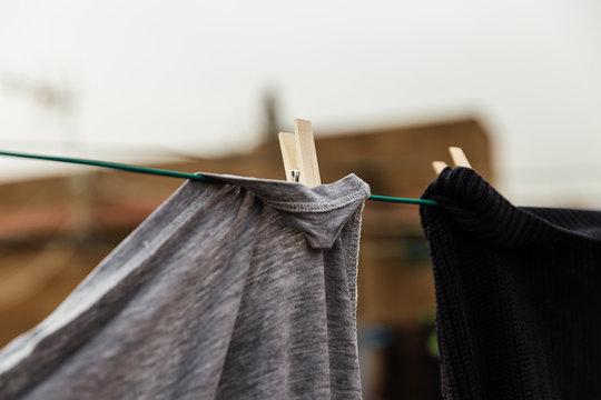 foto sin personas de ropa tendida secandose en un tejado en el exterior, día nublado soleado, camisetas, chandal, calcetines, cogido con pinzas de tender de madera