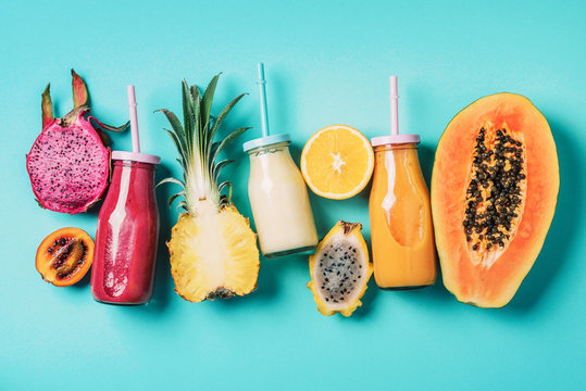 Assortment of colorful smoothie drinks in glass bottle with straw and fruit ingredients - papaya, orange, pineapple, dragon fruit, pitahaya, tamarillo fruit over blue background. Top view, flat lay