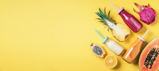 Assortment of colorful smoothie drinks in glass bottle with straw and fruit ingredients - papaya, orange, pineapple, dragon fruit, pitahaya, tamarillo fruit over yellow background. Top view, flat lay Fototapete