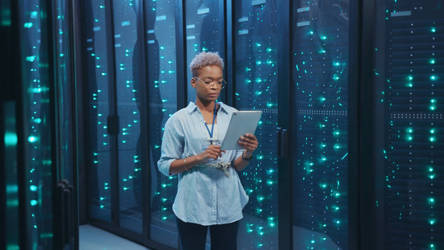 Afro-american female IT administrator walking in server corridor diagnosing hardware system performance in data center cyber secure storage.