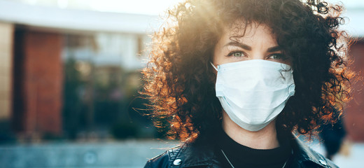Close up portrait caucasian businesswoman with curly hair is looking at camera while wearing a protective mask