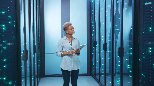 Black female administrator with tablet activating network servers in database digital room. Satisfied woman professional is happy of successful work operation working in data center.