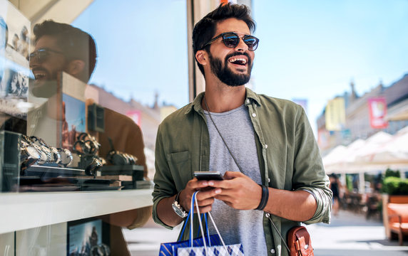 Young man in shopping looking for presents. Consumerism, fashion, lifestyle concept