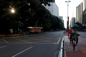 Paulista Avenue is seen empty as delivery men ride their bicycles on the first day of a lockdown imposed by state government because of the coronavirus disease (COVID-19) outbreak, in downtown Sao Paulo