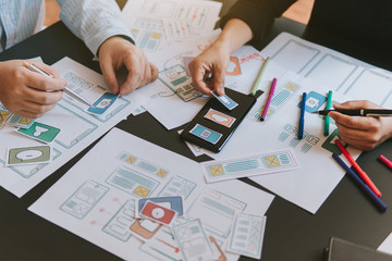Team work meeting of ui/ux designer web application phone prototype