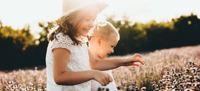 Charming caucasian girl and her small brother walking in a lavender field during a sunset
