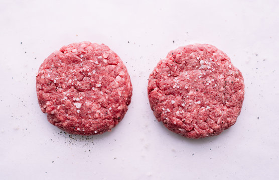 Raw beef cutlets for burgers with salt and pepper on white paper American food