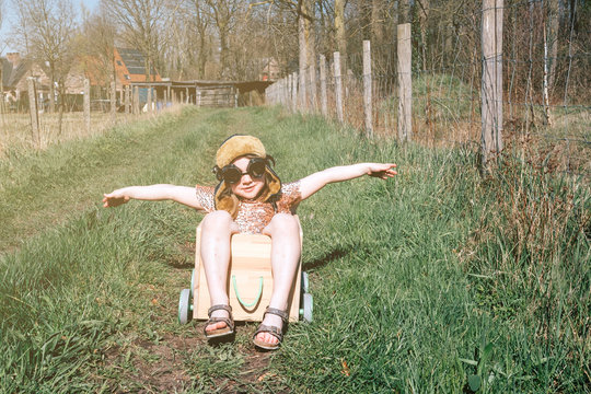 childhood freedom - happy girl with aviator cap dreaming of flying in a wooden box with wheels
