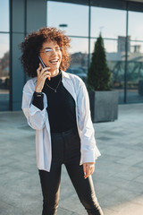 Curly haired business person talking on phone while smiling and wearing glasses outside