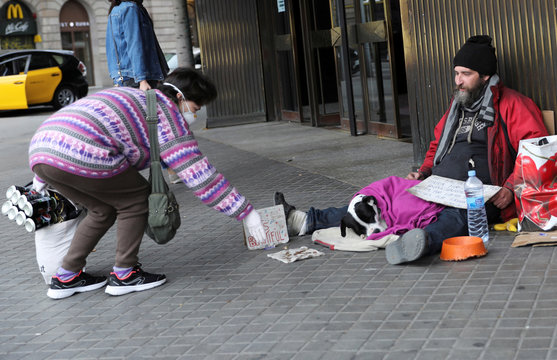 Alessandro from Italy, a homeless man accompanied by his dog Otto, asks for alms as a woman wearing a protective face mask gives him money at the entrance of a supermarket, during the coronavirus disease (COVID-19) outbreak, in Barcelona