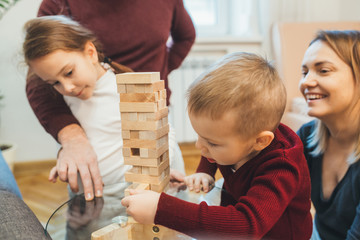 Caucasian family playing jenga with their kids while spending time together