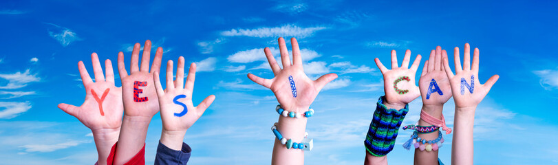 Children Hands Building Colorful Word Yes I Can. Blue Sky As Background