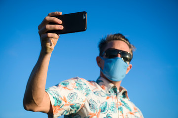 Tourist in colorful Hawaiian shirt wearing a protective face mask standing outdoors taking a selfie on quarantine