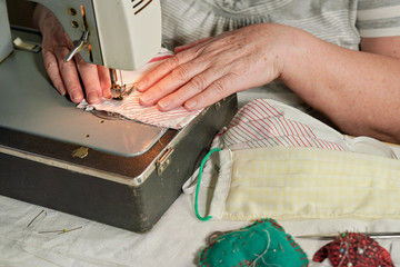 Elderly senior woman working on old sewing machine - making home made face masks against coronavirus spreading, closeup detail on moving needle and fingers holding fabric