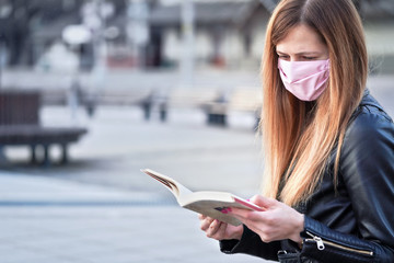 Young woman with hand made pink face nose mouth mask sitting alone, reading book, empty city square...
