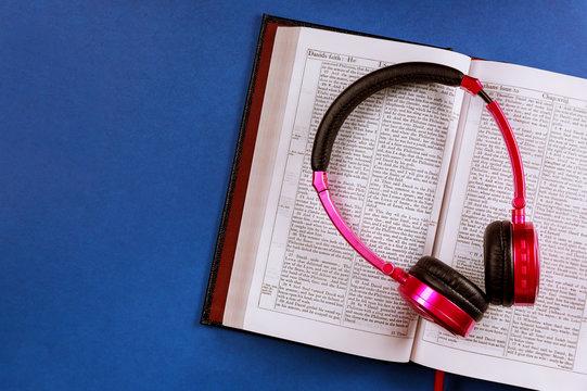 Open Bible on a headphones on religious audiobook