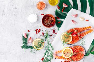 Raw salmon fish fillet with fresh herbs on cutting board