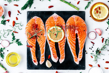 Fresh salmon fillet with aromatic herbs and spices- healthy food, diet or cooking concept.