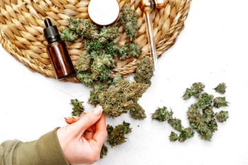 Hands holding Cannabis Buds. Medical marijuana oil