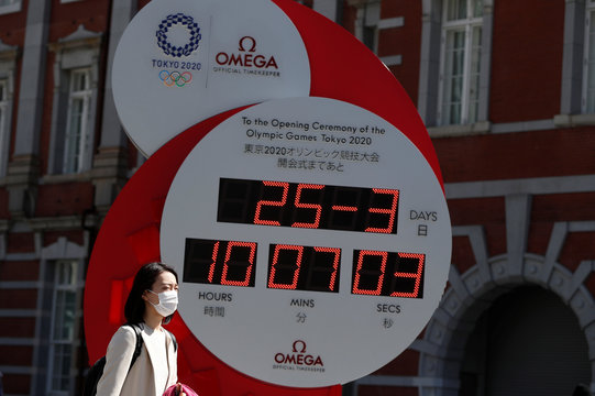 A woman wearing a protective face mask due to the outbreak of coronavirus disease (COVID 19) walks next to Omega clock for the Tokyo 2020 Olympic Games after the announcement of the games' postponement to the summer of 2021, in Tokyo