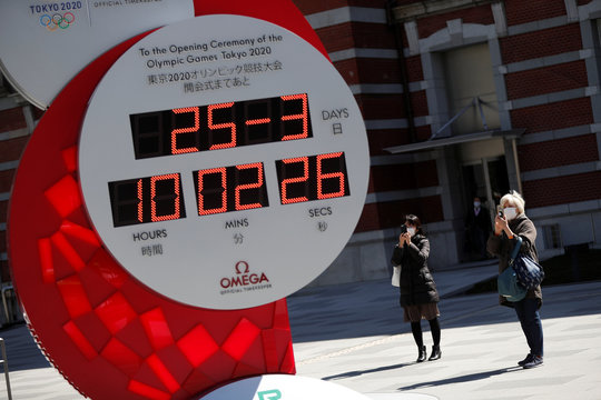 People in protective face masks due to the outbreak of coronavirus disease (COVID 19) walk next to Omega clock for the Tokyo 2020 Olympic Games after the announcement of the games' postponement to the summer of 2021, in Tokyo